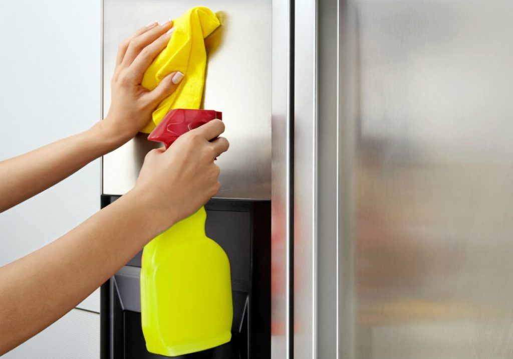 Cleaning a refrigerator's stainless steel door with a yellow cloth