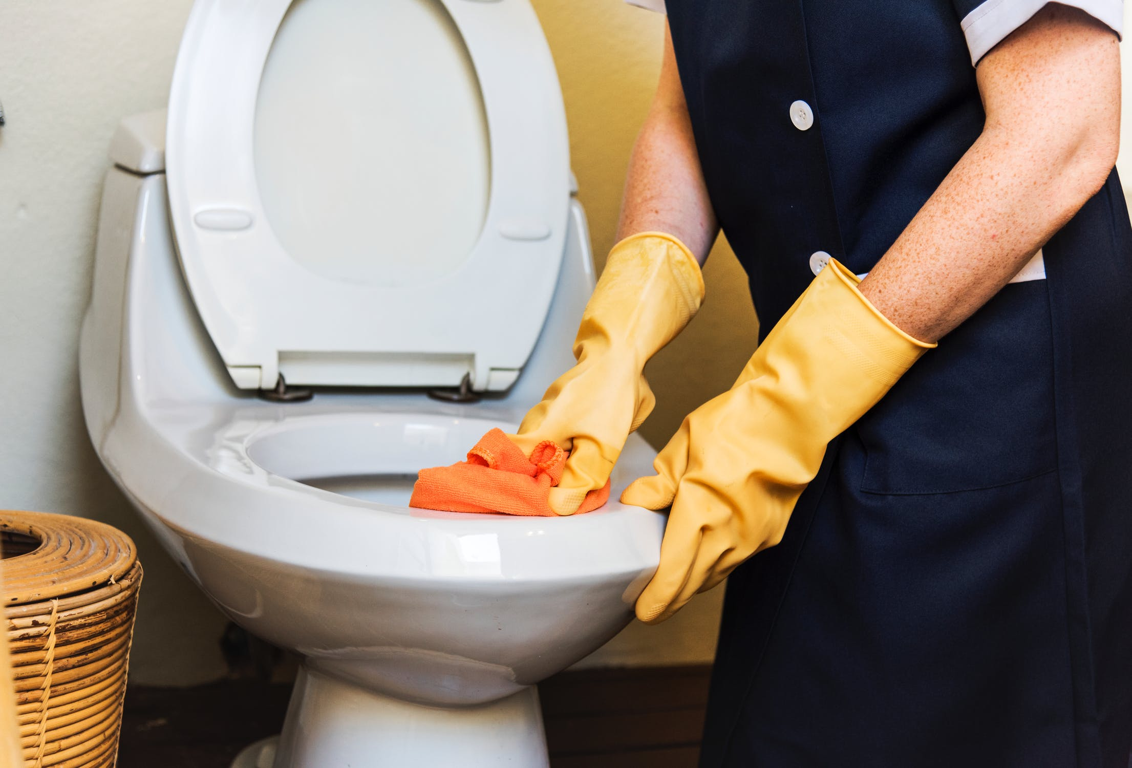 cleaning toilet with wearing yellow gloves
