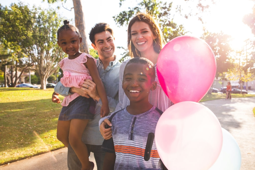 White couple with their black kids smiling and holding balloons