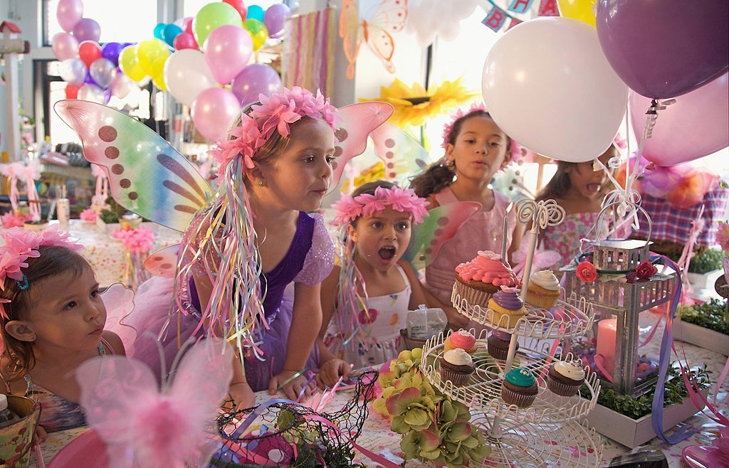 Small children enjoying in a party with multicolored balloons, cupcakes and other party items
