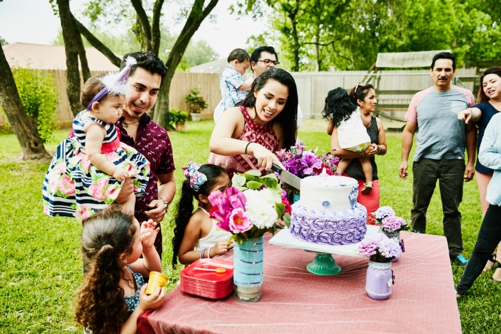 Couples gathered in a lawn with their kids to witness a lady cutting cake