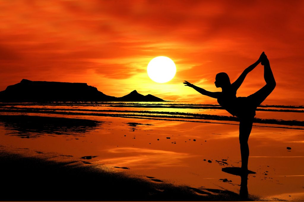 A young girl doing yoga on a beach with sunset and orange yellow clouds