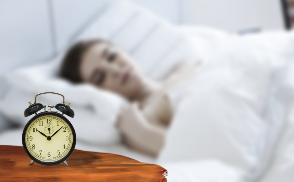 Girl sleeping with a white sheet and an alarm clock on table