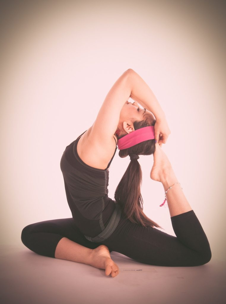 A young girl in black dress performing a variation of pigeon pose