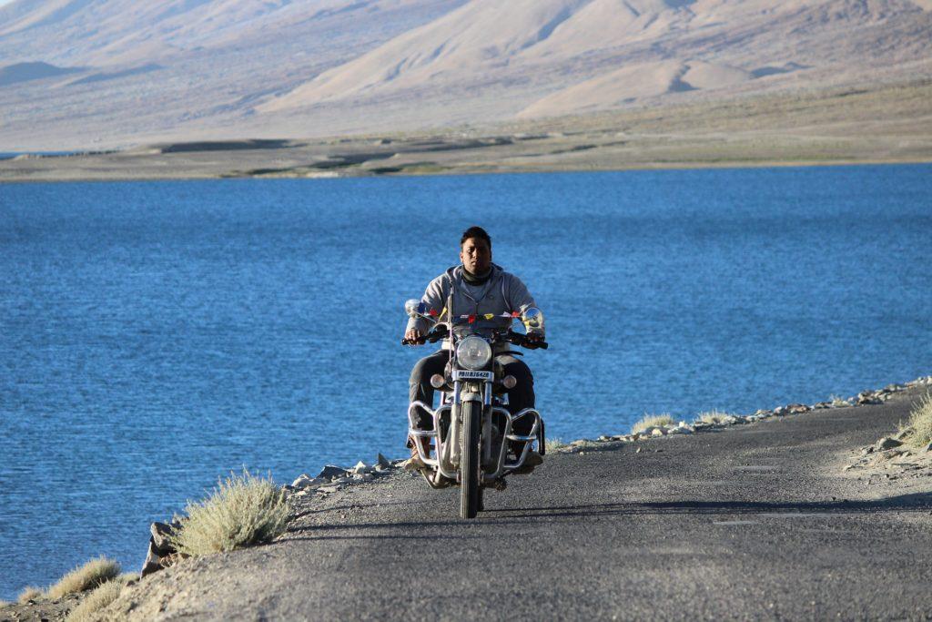 A man on a bike riding to Pangong Lake
