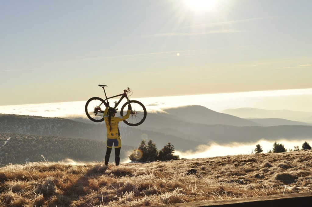 Woman lifting her cycle overhead on the top of a mountain