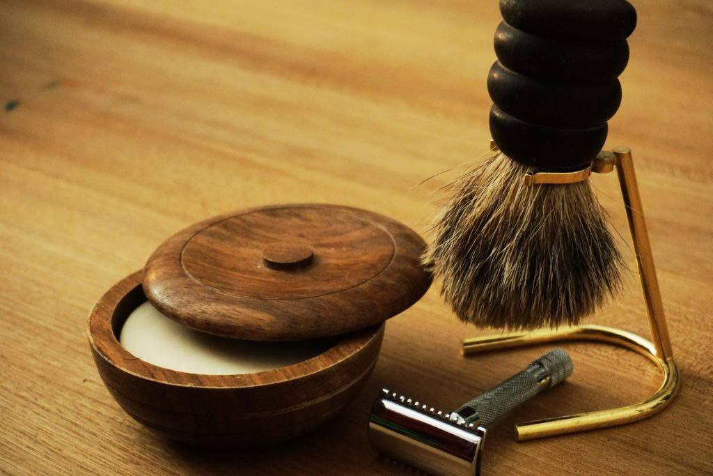 Grooming kit essentials including razor, cream and brush on a wooden table